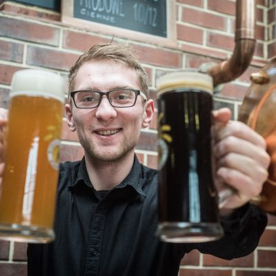 smiling man with pints of beer in warzelnia in bydgoszcz