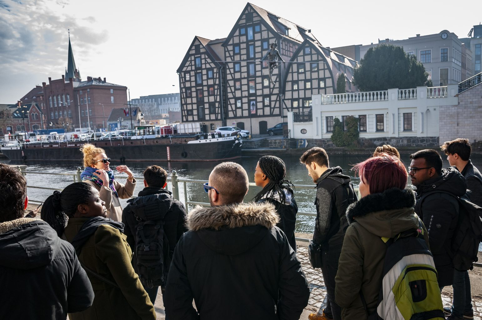 people listening a guide in front of granaries in bydgoszzcz