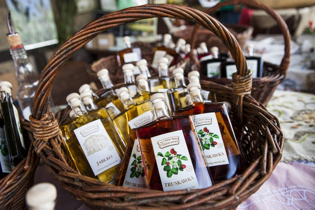 small bottles with fruit syrup in the basket on the farm food festival in gruczno
